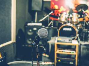 Selective focus on microphone with blurry music studio background, vintage style