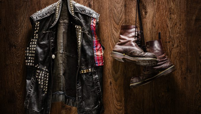 Punk-rock leather jacket and a pair of old boots hanging on a wooden wall